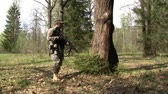airsoft : Moscow, Russia - May 09, 2013: Airsoft player is in position in the forest. Sports team game using a copy of a firearm. People in military uniforms with weapons at the exercises.