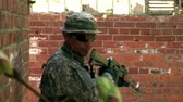 airsoft : Moscow, Russia - May 09, 2013: Players of airsoft walks near the brick wall. Sports team game using a copy of a firearm. People in military uniforms with weapons at the exercises. Stock Footage