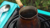 metal powder : Boiled Coffee Praparing in Vintage Bronze Turka at outdoors Stock Footage