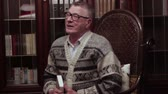 Old man with glasses cheerful grandfather remembers the youth on a rocking chair near the bookcase 4 Stock mozgókép