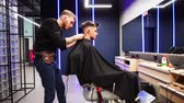 Lipetsk, Russian Federation - January 28, 2018: Charlies Barbershop. Male Barber trimmer cuts the young man in the Barber shop