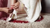 tkanička : Bridesmaid helps in getting dressed wedding shoes