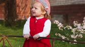 pretty : Little girl standing near fence in nature smiling and happy Stock Footage