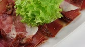 serrano : Traditional Spanish ham (jamon) in white plate (loop) Stock Footage
