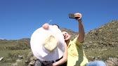 ouvido : A pair of young people doing selfie on a background of mountains close-up slow motion.