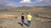 ouvido : A pair of lovers walking through picturesque hills holding hands 4k. Stock Footage