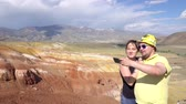 ouvido : A couple of newlyweds doing selfie on the background of the mountains 4k close-up.