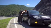 ouvido : A tourist girl hitchhiking a car on a mountain road and sits down in it 4k. Stock Footage