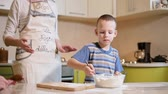 6 year old boy helps mom to cook in the kitchen.