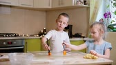 Boy and girl prepare the cake in the kitchen