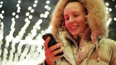 Attractive Woman using Mobile Phone During Walk on Streets of Night Town.