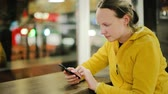 Attractive young woman with smartphone in cafe Stock Footage