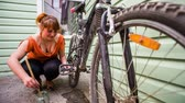 oiling : In the frame there is a young girl sitting on her hunkers and carefully washing and cleaning her bike with the help of brush and some liquid in the bottle.