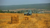 mechanized : This is a front shot of a light blue farm tractor slowly moving along golden stubble field collecting straw with ready bales lying around. Stock Footage