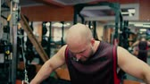 Man in gym doing pulls weight on cable machine