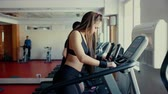 The girl with long hair walking, running on treadmill gym workout