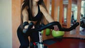 Beautiful brunette girl with long hair rides a bicycle in a gym