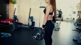 kas inşa : Young beautiful girl with long hair in the gym doing exercises on the squat with a barbell. 4 k