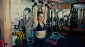 Young sports woman brunette with long hair doing exercises with dumbbells in the gym. 4 k