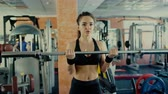 Young sporty woman brunette with long hair lifting barbell bar in gym. Stock Footage
