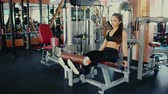 Young beautiful girl brunette with long hair doing exercises for legs muscles in gym.