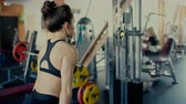Young beautiful brunette girl wih long hair in the gym doing exercise on machine at gym video.