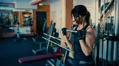 Beautiful sporty brunette middle aged woman blifting barbell bar in gym. Stock Footage
