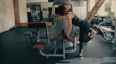csikk : Sporty beautiful brunette middle aged woman doing exercises for legs and buttocks muscles in gym