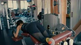 Sporty beautiful brunette middle aged woman doing exercises for legs and buttocks muscles in gym