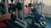 Beautiful sporty brunette middle aged woman doing squat workout in gym. Stock Footage