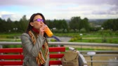 den : Young beautiful woman drinking orange juice outdoors at summer park. Dostupné videozáznamy