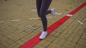 young : Young beautiful woman is running in the Park. Close up of running shoes and legs in action. slow-motion