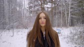 coat : Close up Portrait of stylish young beautiful woman walking outdoors in a winter park over snowy background. It is snowing. beautiful young woman is walking in a winter park. looking to the camera. 4 k Slow motion. She is happy in winter. Smiling. Winter p Stock Footage