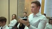 teach : The listener in the audience pulls his hand to ask a question. Question from the audience. A man in the audience asks a question to speaker. Stock Footage