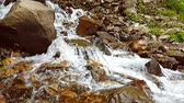 hidratar : Slow motion of a small mountain waterfall. 240fps. The mountain stream falls down on stones in a bottom. Vídeos