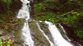 hidratáció : Slow motion of a small mountain waterfall. The mountain stream falls down on stones in a bottom. Stock mozgókép