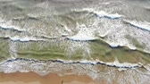 yellowstone : Background or texture. Aerial view ocean waves come to the shore, and wash the red yellow sand. Height view.