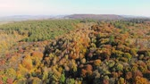Aerial Footage View. Colored autumn trees. Flight over autumn mountains with forests, meadows and hills in sunset soft light.