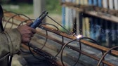An employee welds a metal structure on a construction site. Construction works. Work outdoor