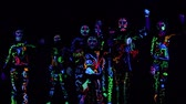group of children performs performances in a dark hall, in colorful costumes. Paint in costumes shines in the dark. Choreographic setting of a group of children