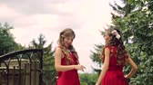 Two girls in red dresses dance and improvise a good mood and smile. Happy girls smile.