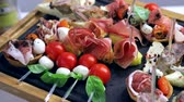 frankfurters : Sandwich canapes on the buffet table. Red tomatoes with mozzarella cheese with herbs and sausage with bread
