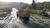 dumper : A truck of kamaz loaded with construction debris goes to the swamp. Construction site after rain.