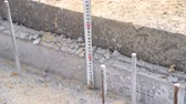 laminat : builder measures the height of concrete at construction site