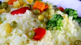 kırmızı biber : Rice with slices of vegetables close-up, greens and red pepper on a white plate spinning Stok Video