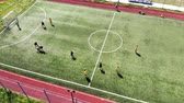 tribunal : Aerial view children play football on a small football field. Modern football ground near the school