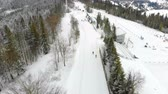 narciarz : Aerial drone shot of Skiers pass the track in winter in the fabulous mountains. The forest is covered with snow and piste skiing
