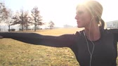 bisiklete binme : Fitness model completes yoga moves on a sunshine day in the park wearing headphones.