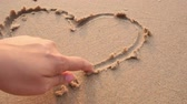 san valentin corazones : Close up females hand drawing heart shape on wet and clean sand of the sea beach in slow motion. Outdoor shooting in natural daylight. Nature, environment conservation, love, togetherness concepts.