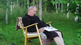 голова и плечи : Senior Man in Bath Robe Sleeping in Rocking Chair Outdoors with Book in Hands Стоковые видеозаписи